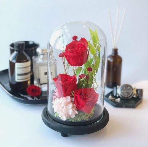 Sparks Fly consisting of three red preserved roses, hydrangeas and foliage.