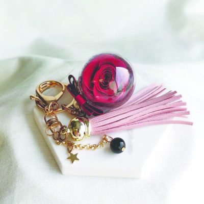 Charm featuring a preserved scarlet rose with pink leather tassels and onyx gemstone
