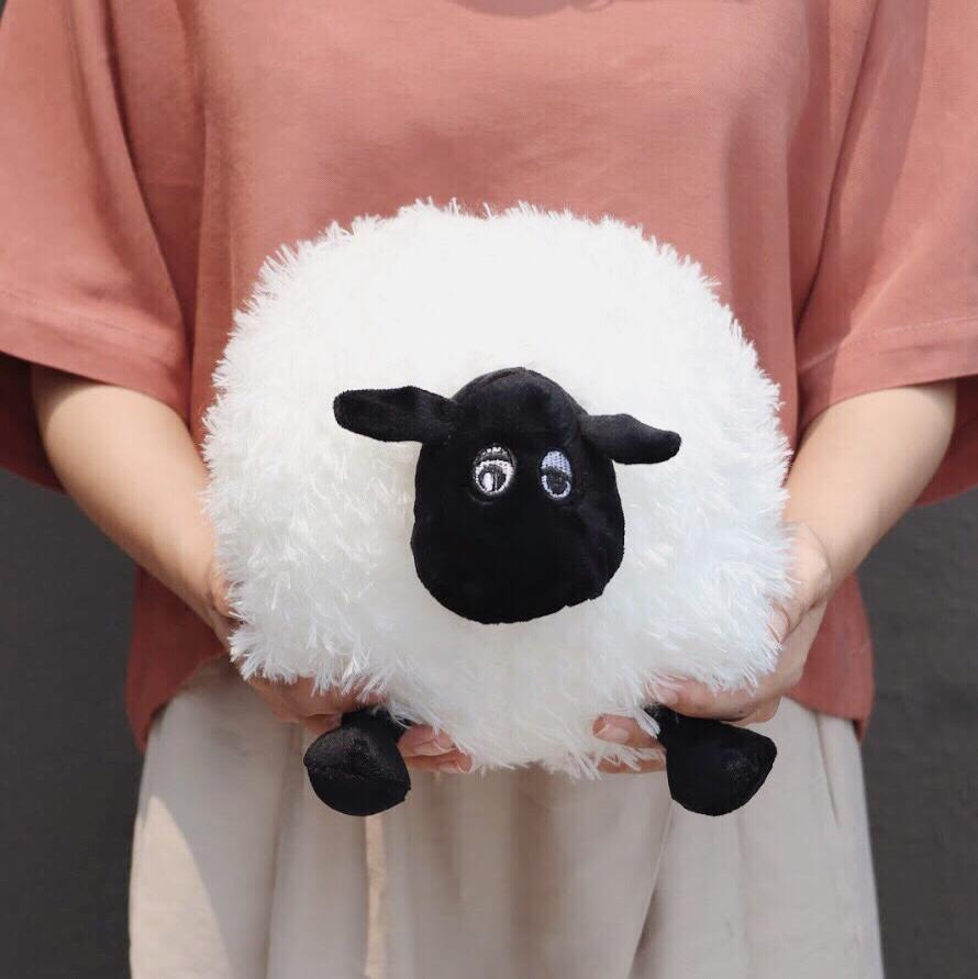 A woman in reddish-brown top and cream pants holding Sheep plushie