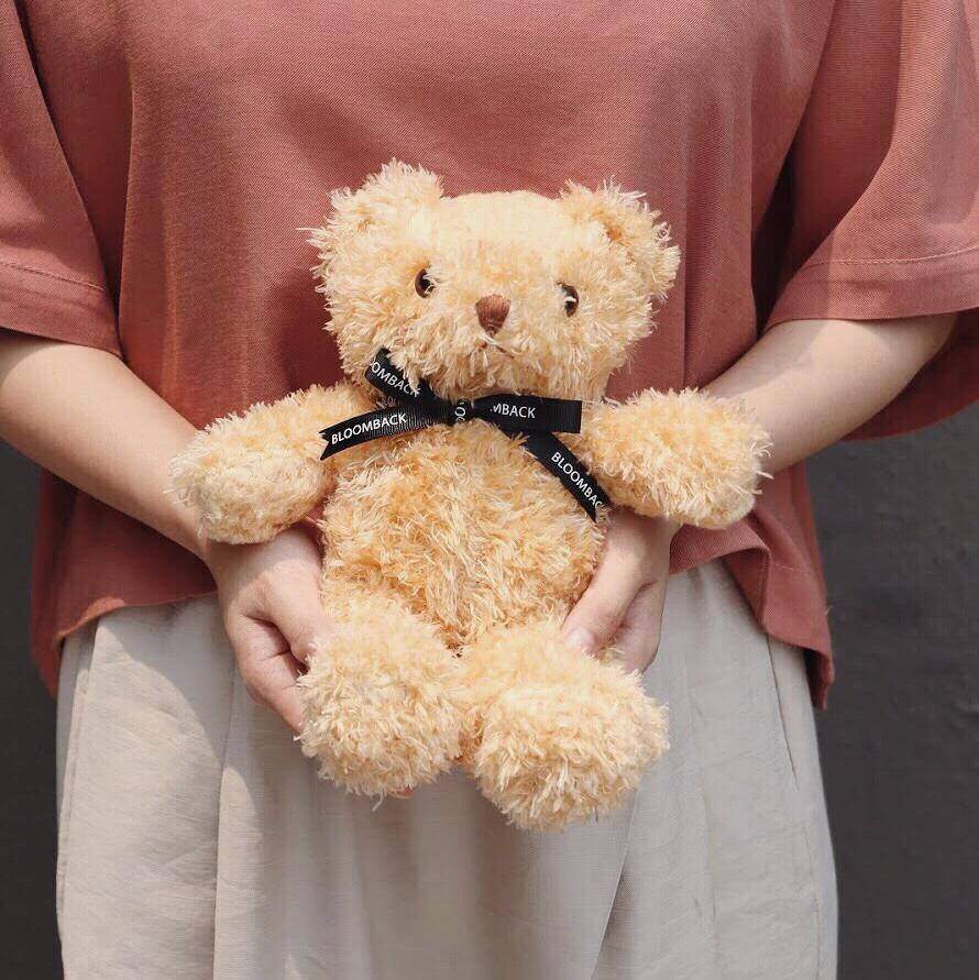 A woman in reddish-brown top and cream pants holding bear plushie