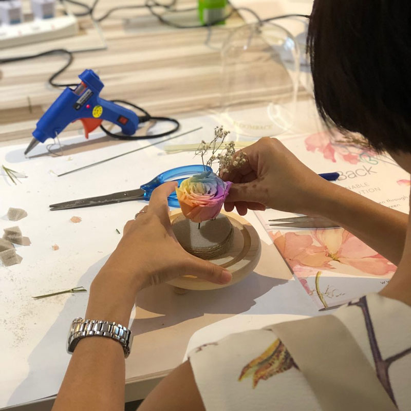 Participant crafting a preserved flowers arrangement for a glass dome