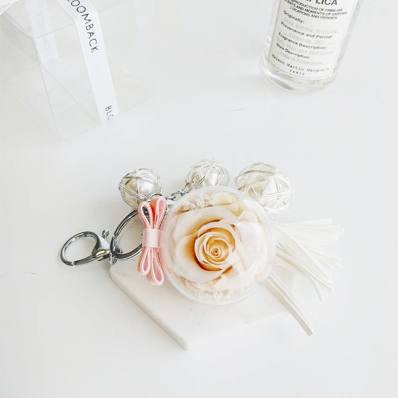 A charm keychain featuring 1 champagne preserved rose, white tassels, triple pearls and BloomBack tag.