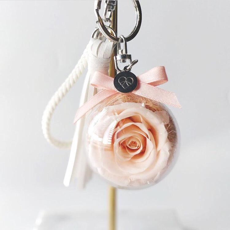 Bag charm featuring champagne preserved rose in acrylic ball