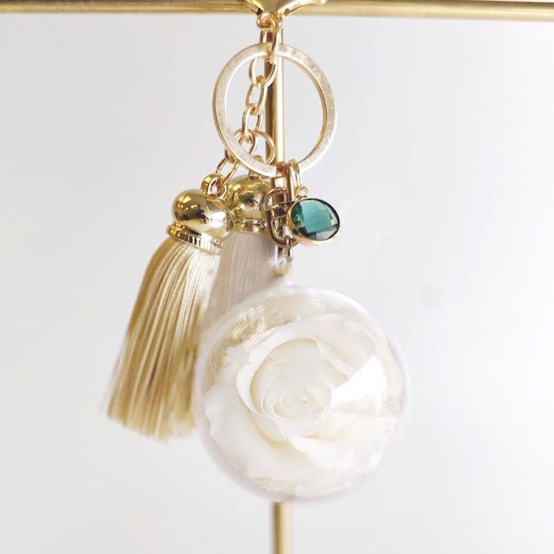 A charm keychain featuring 1 white preserved rose, birthstone, string tassels and BloomBack tag.
