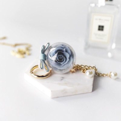 A petite charm keychain featuring 1 space grey preserved rose, chain accessory and BloomBack tag.