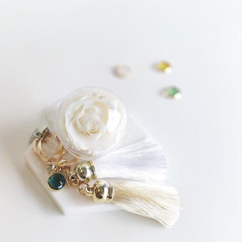 A charm keychain featuring 1 white preserved rose, white string tassels, birthstone charm and BloomBack tag.