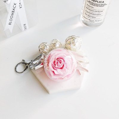 A charm keychain featuring 1 light pink preserved rose, triple pearls and BloomBack tag.