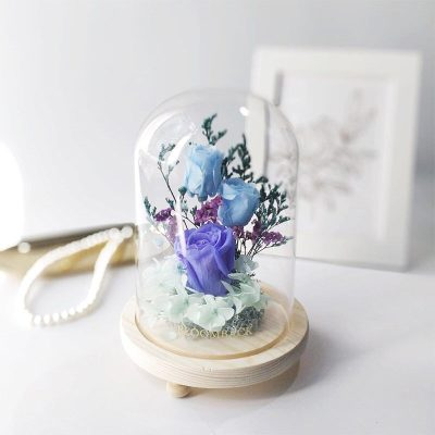 A medium glass dome featuring 1 violet preserved rose , 2 sky blue preserved rose, blue preserved moss, teal preserved hydrangeas and preserved foliages.