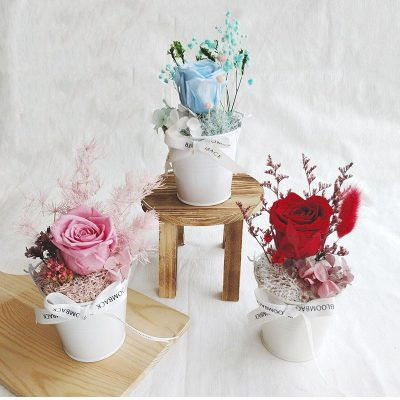 A small white bucket featuring red, pink and blue preserved rose, preserved foliages, preserved hydrangeas and BloomBack ribbon.