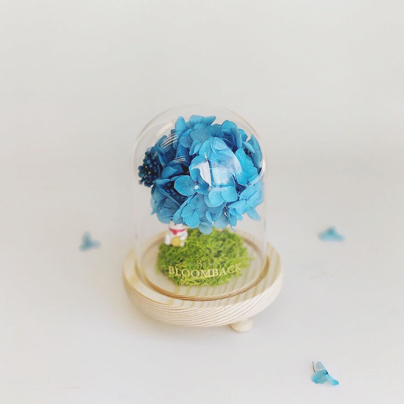 A lookalike tree made of blue hydrangeas in a small glass dome.