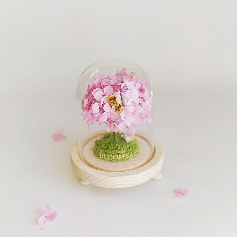 A lookalike tree made of pink hydrangeas in a small glass dome.