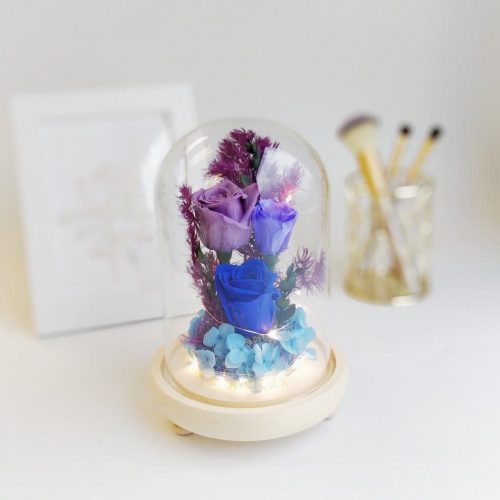 A medium glass dome featuring 1 royal blue preserved rose, 1 violet preserved rose, 1 lavender preserved rose, blue preserved hydrangeas, preserved foliages and LED lights.