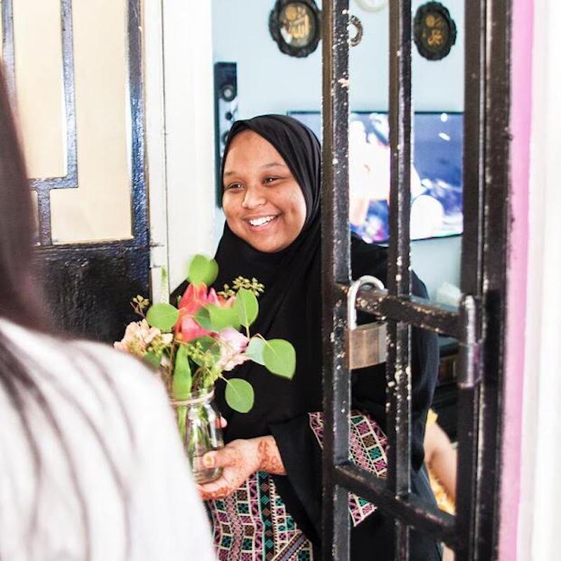 A women receiving a bouquet of flowers with a big smile.