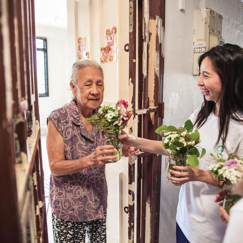 A women giving out repurposed flowers to an elderly.