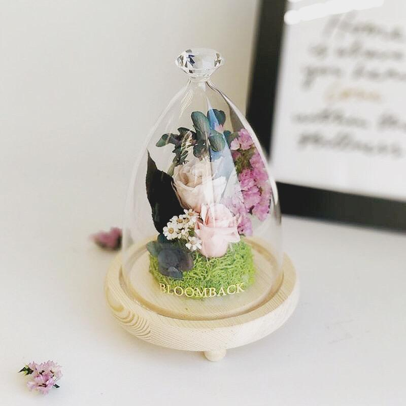 A small diamond glass dome featuring 1 khaki preserved rose, 1 light pink preserved rose, green preserved moss and preserved foliages.