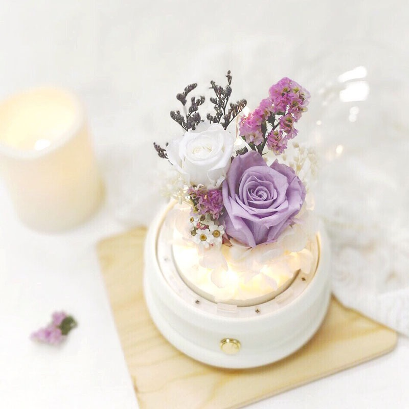 A white bluetooth dome featuring 1 lavender preserved rose, 1 white preserved rose, white preserved hydrangeas and preserved foliages.