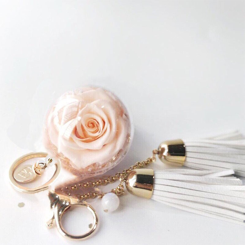 A charm keychain featuring 1 champagne preserved rose , gemstone, white leather tassels and BloomBack tag.