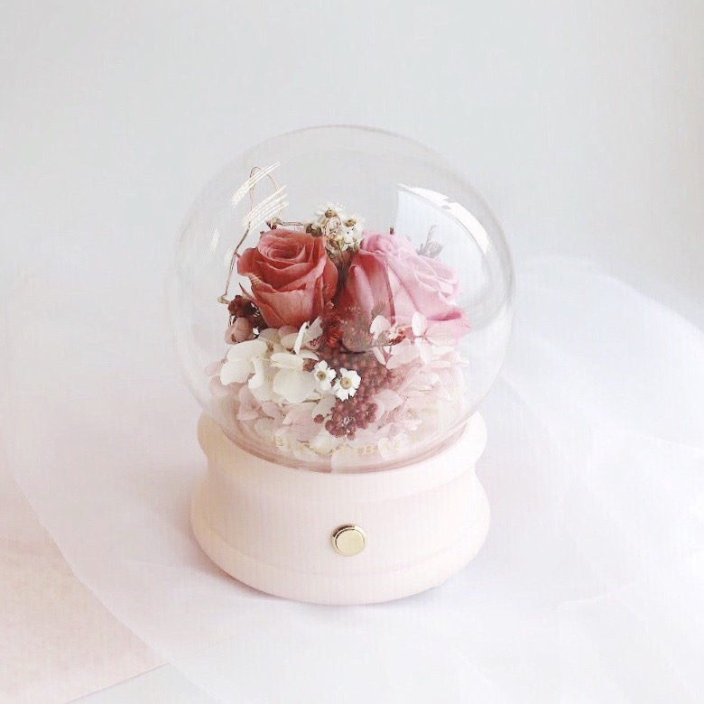 Floral arrangement featuring 2 pink preserved roses encased in glass dome with bluetooth speaker embedded inside